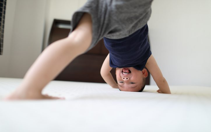 Energetic young boy jumping on bed