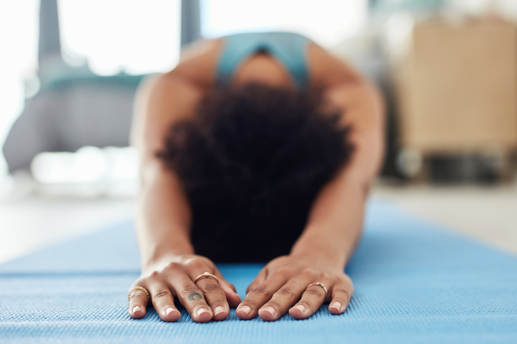 Woman doing yoga on a blue mat at home