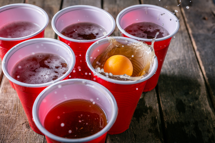 Beer pong, drinking game, ping pong ball splashing down into red plastic cup of beer