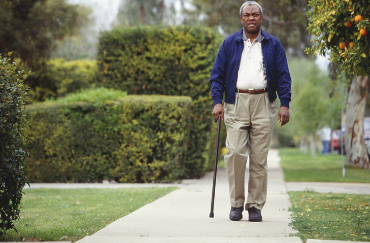 Man walking with cane in park