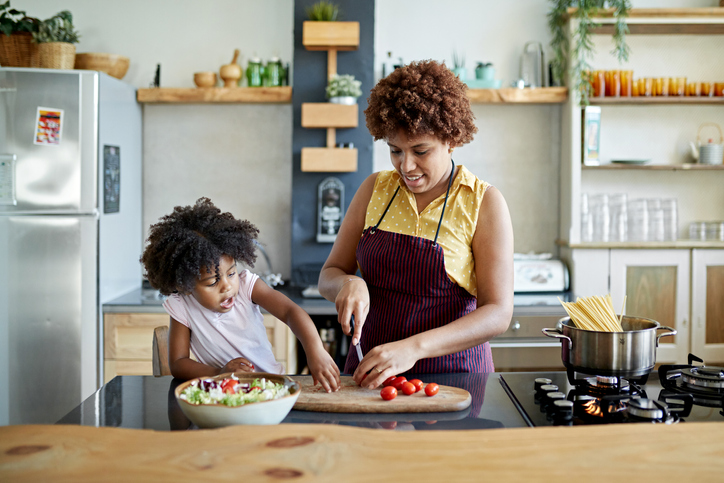 Mother and young daughter preparing dinner